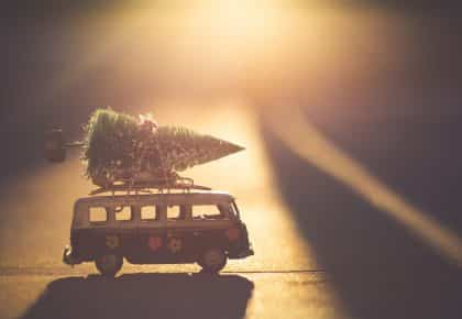 Van miniature transportant un sapin pendant la golden hour